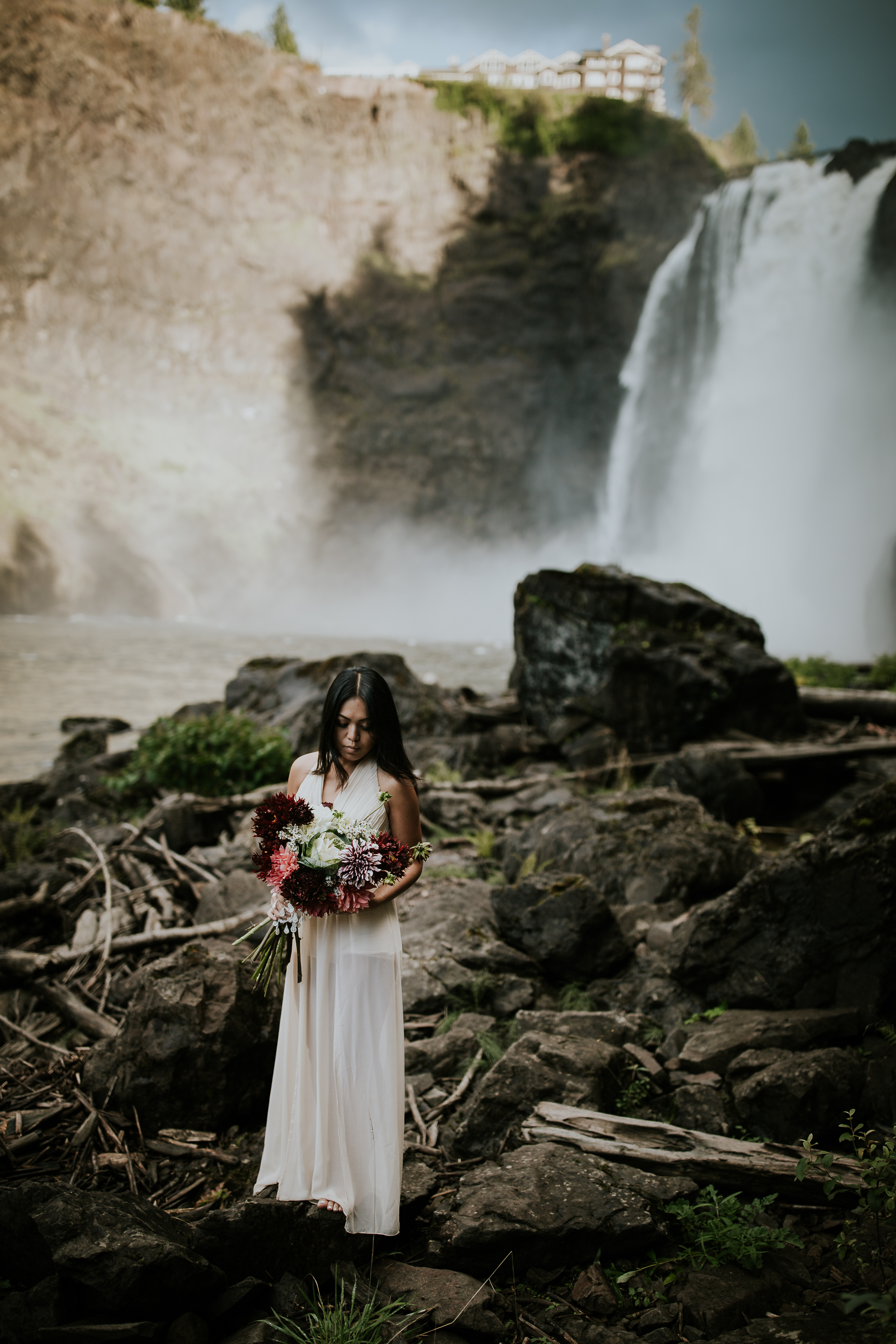 Adventurous bride standing on rocks holding bouquet near Snoqualmie Falls
