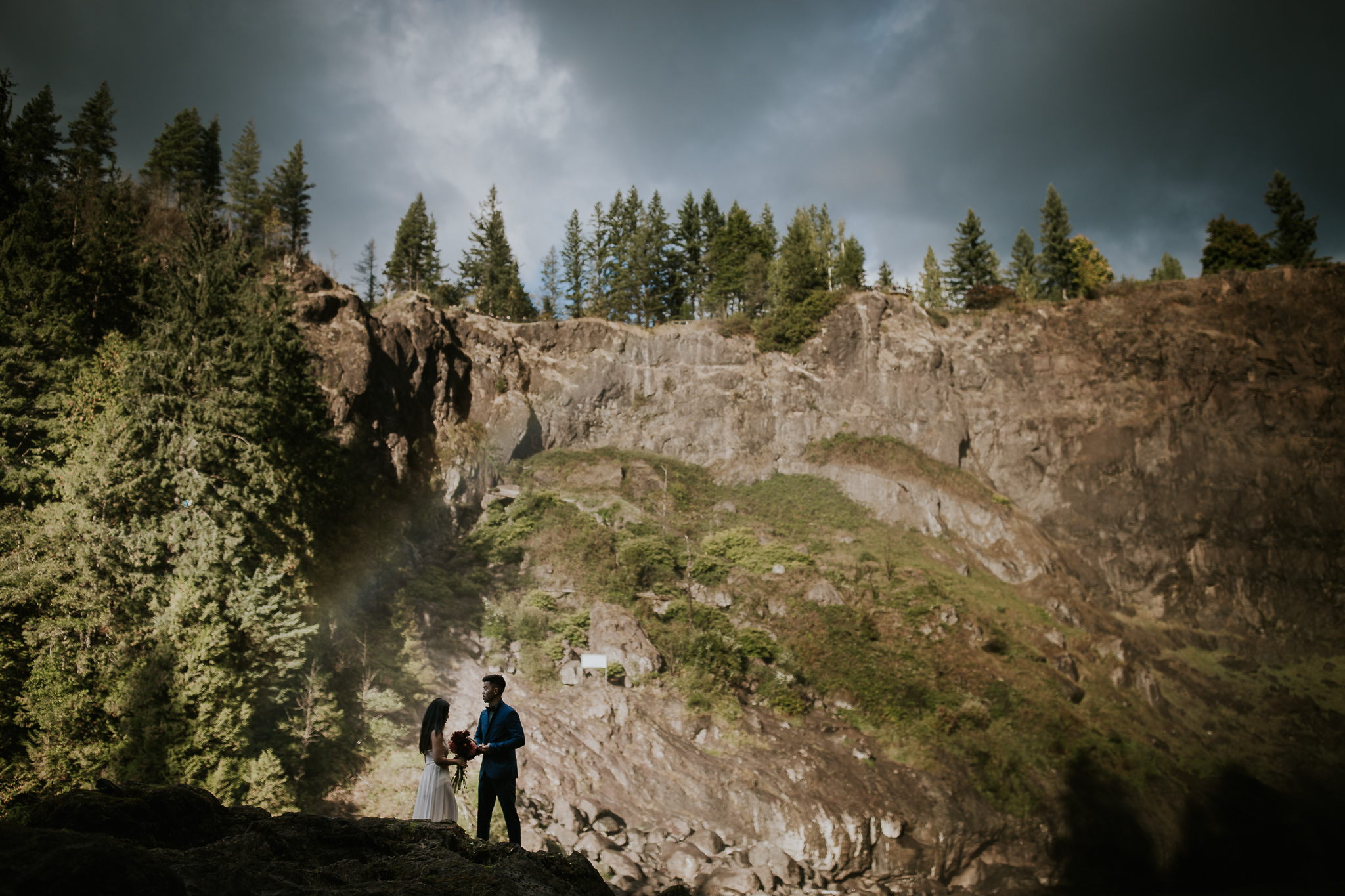Adventurous bride and groom silhouetted against Snoqualmie falls canyon