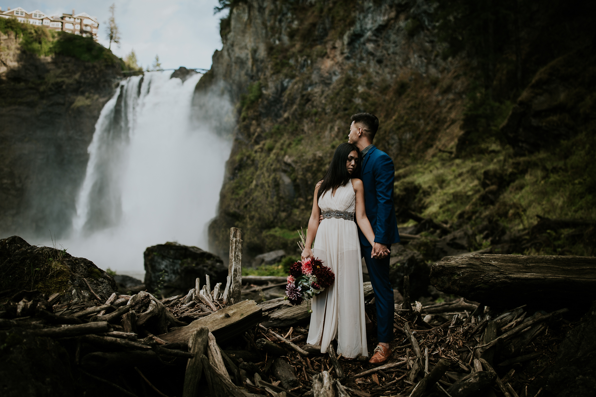 Bride and groom holding hands among logs in front of Snoqualmie falls