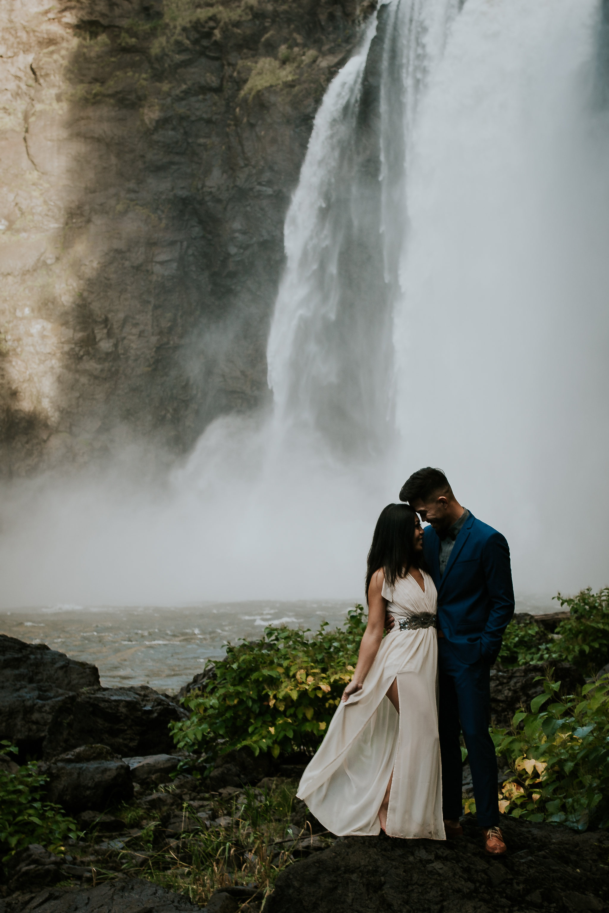 Eloping couple standing at the base of Snoqualmie Falls