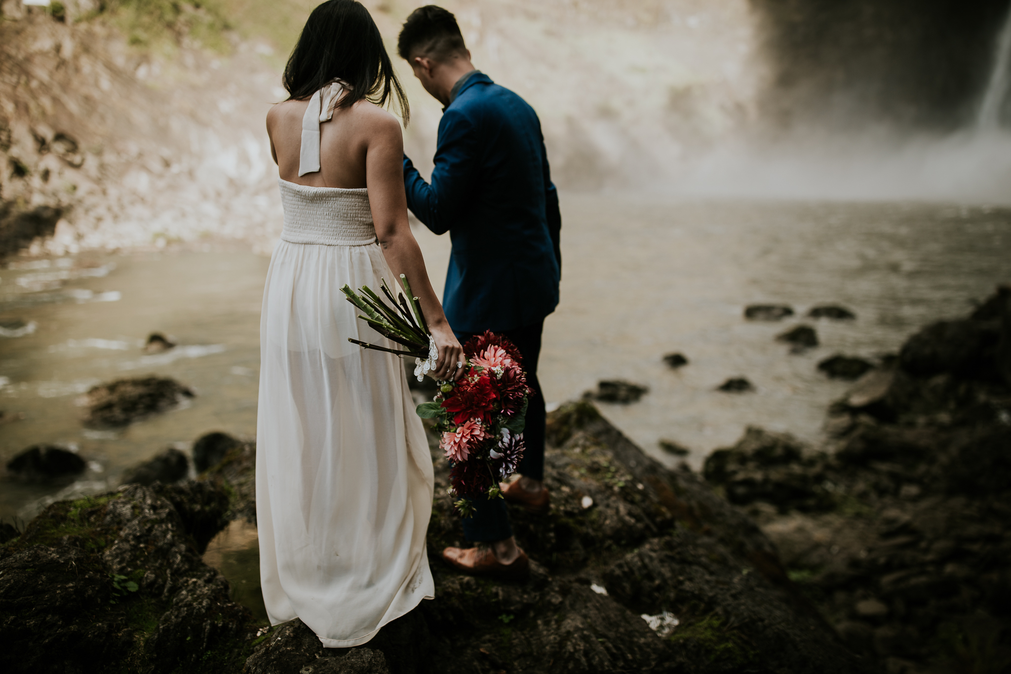 Groom leading bride across rocks to waterfall elopement