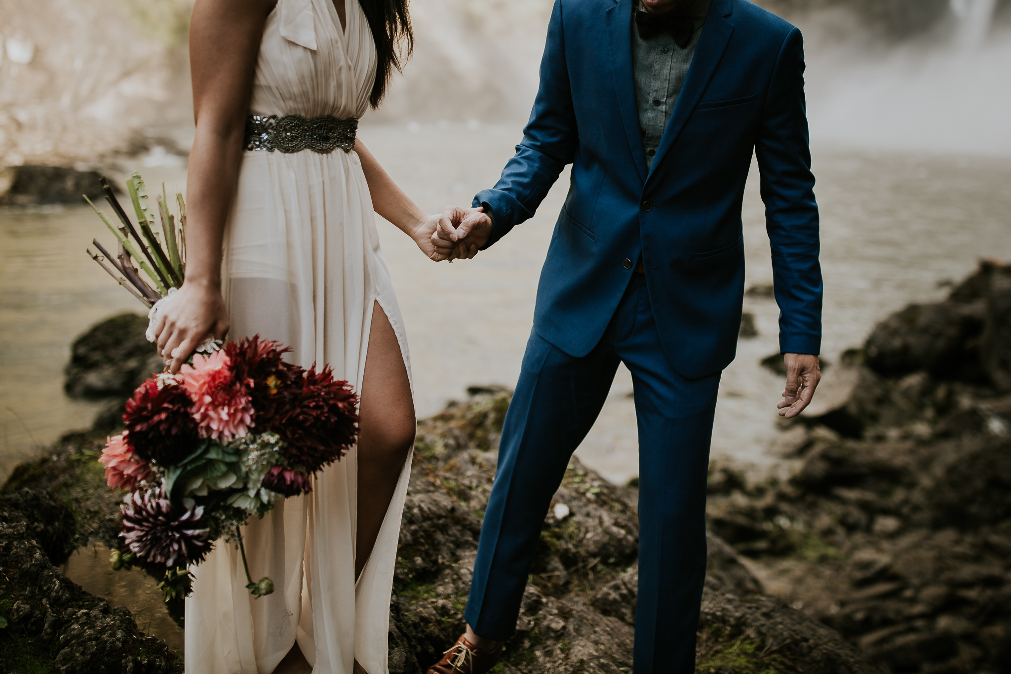 Bride and groom holding hands standing on rocks near waterfall elopement