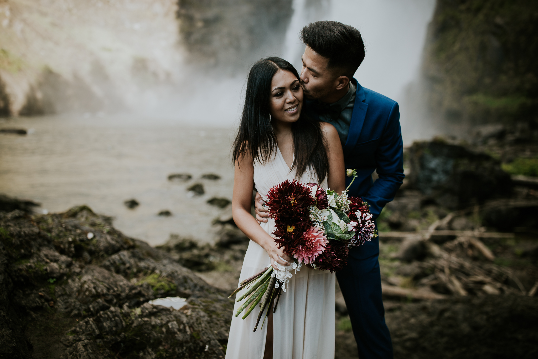 Adventurous bride holding bouquet and groom in blue suit near Snoqualmie Falls