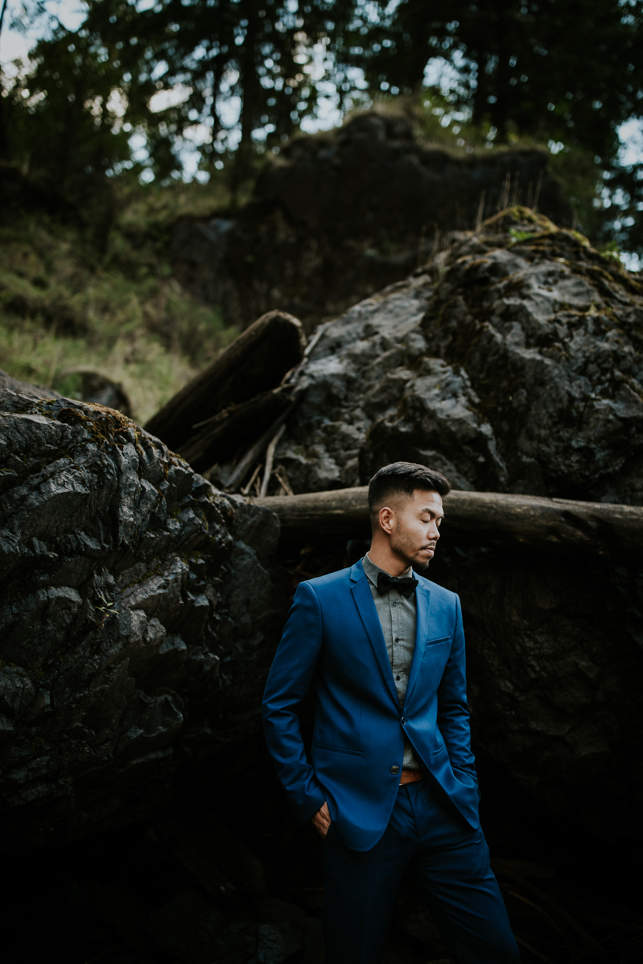 Groom wearing blue suit standing in front of black rocks at Snoqualmie falls elopement