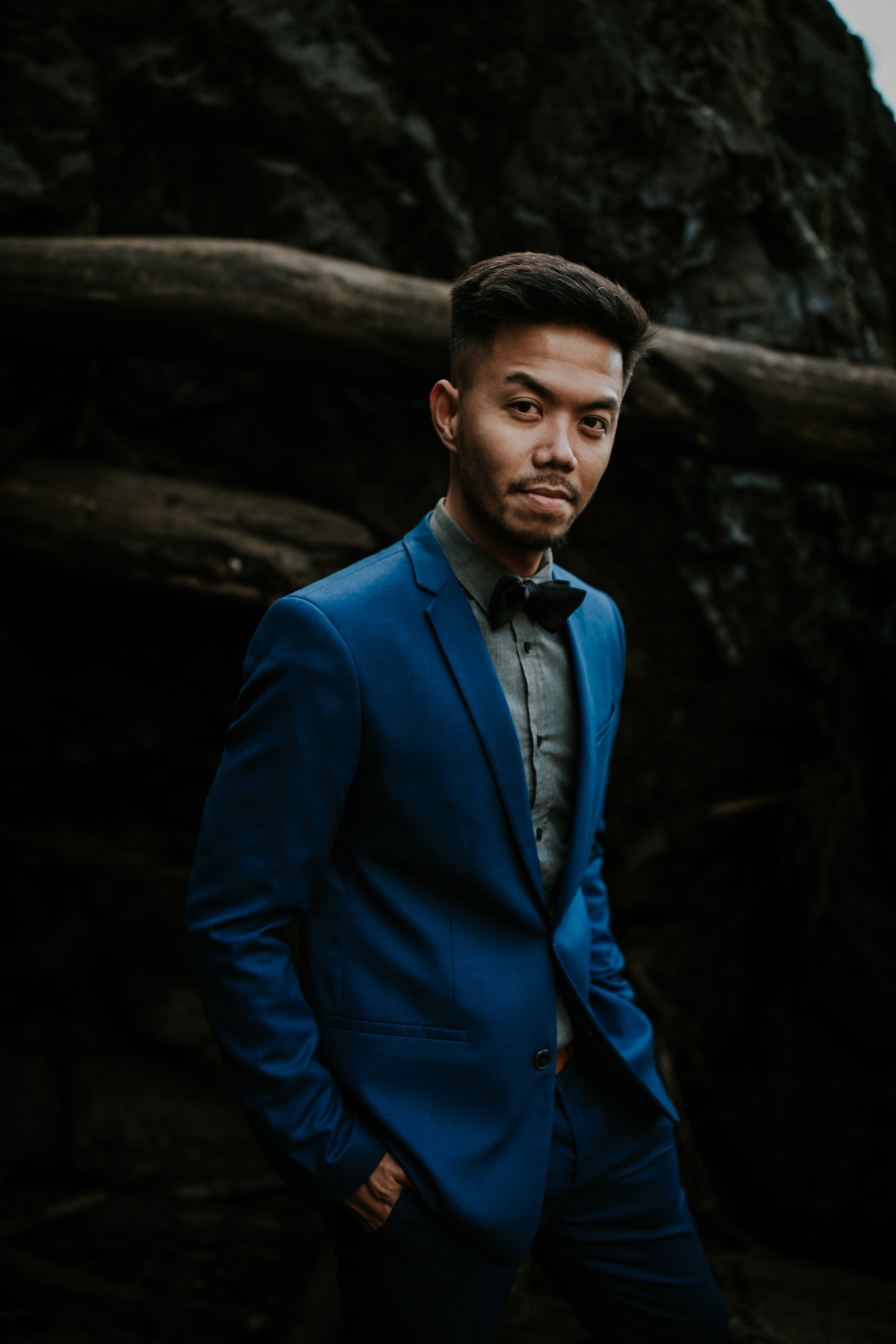 Adventurous groom wearing blue suit in front of rocks at waterfall elopement
