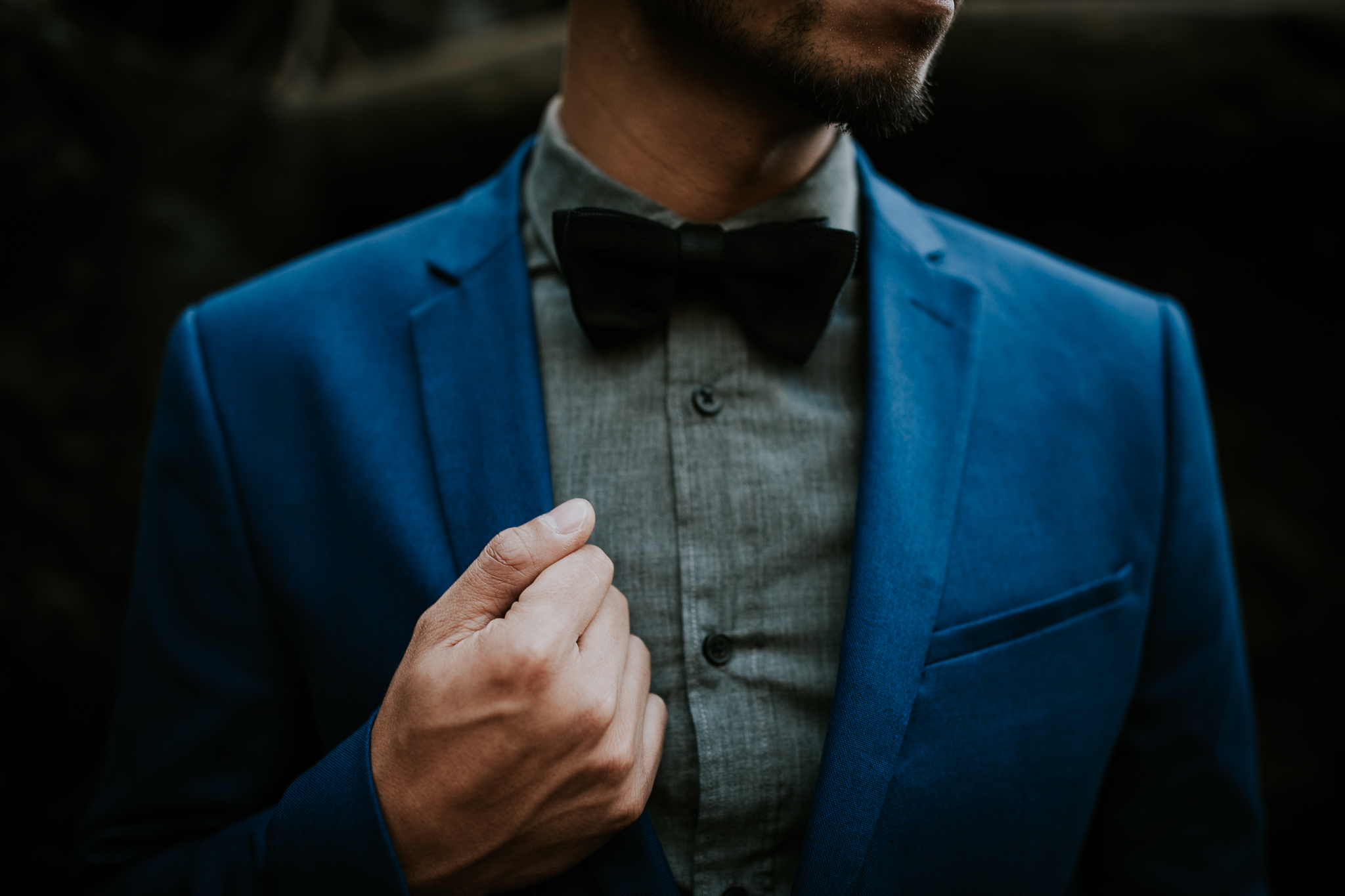 Close up of groom holding his blue suit at adventurous waterfall elopement near Seattle
