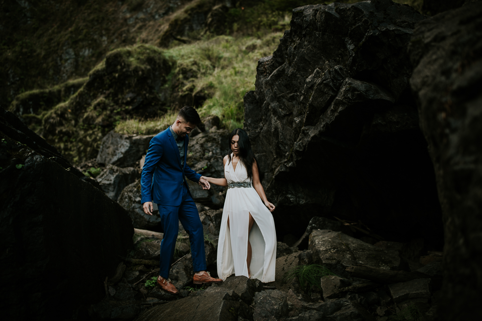 Bride and groom holding hands and laughing at adventurous waterfall elopement near Seattle