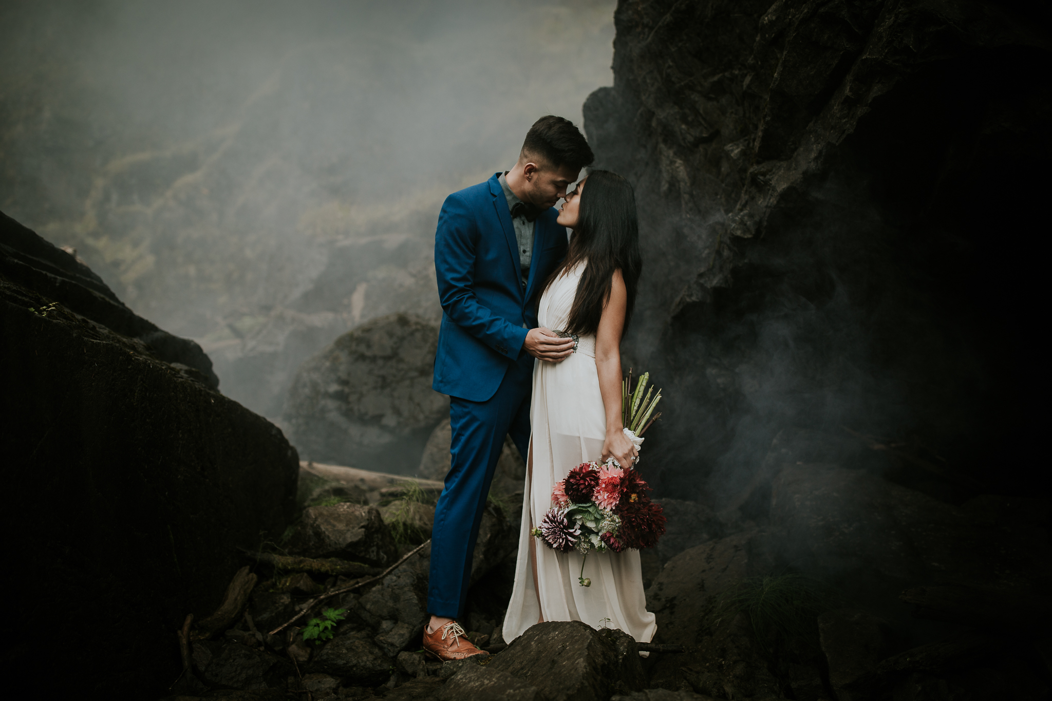 Bride and groom embracing in front of black rocks with mist near waterfall