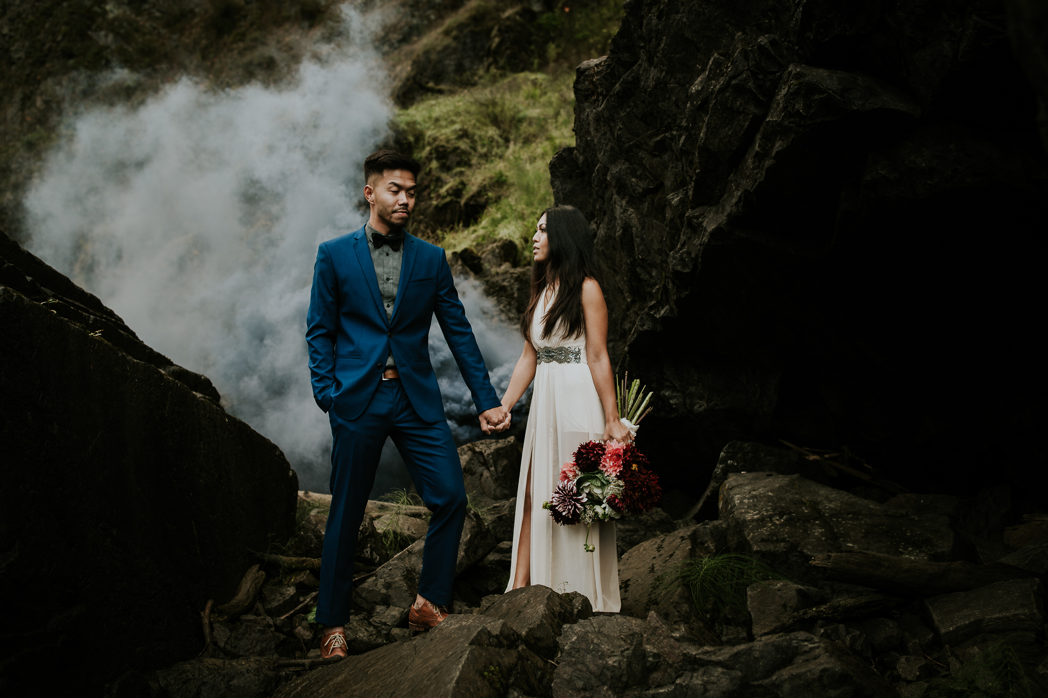Bride and groom holding hands as smoke bomb goes off in background at waterfall elopement