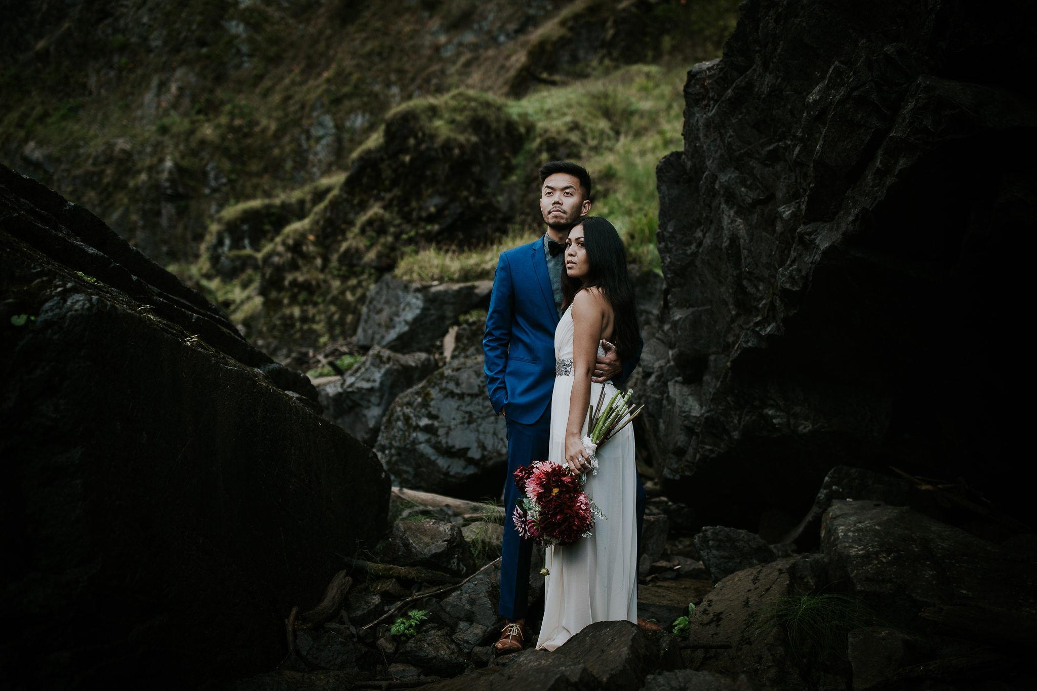Bride and groom looking majestically out at Snoqualmie falls during elopement