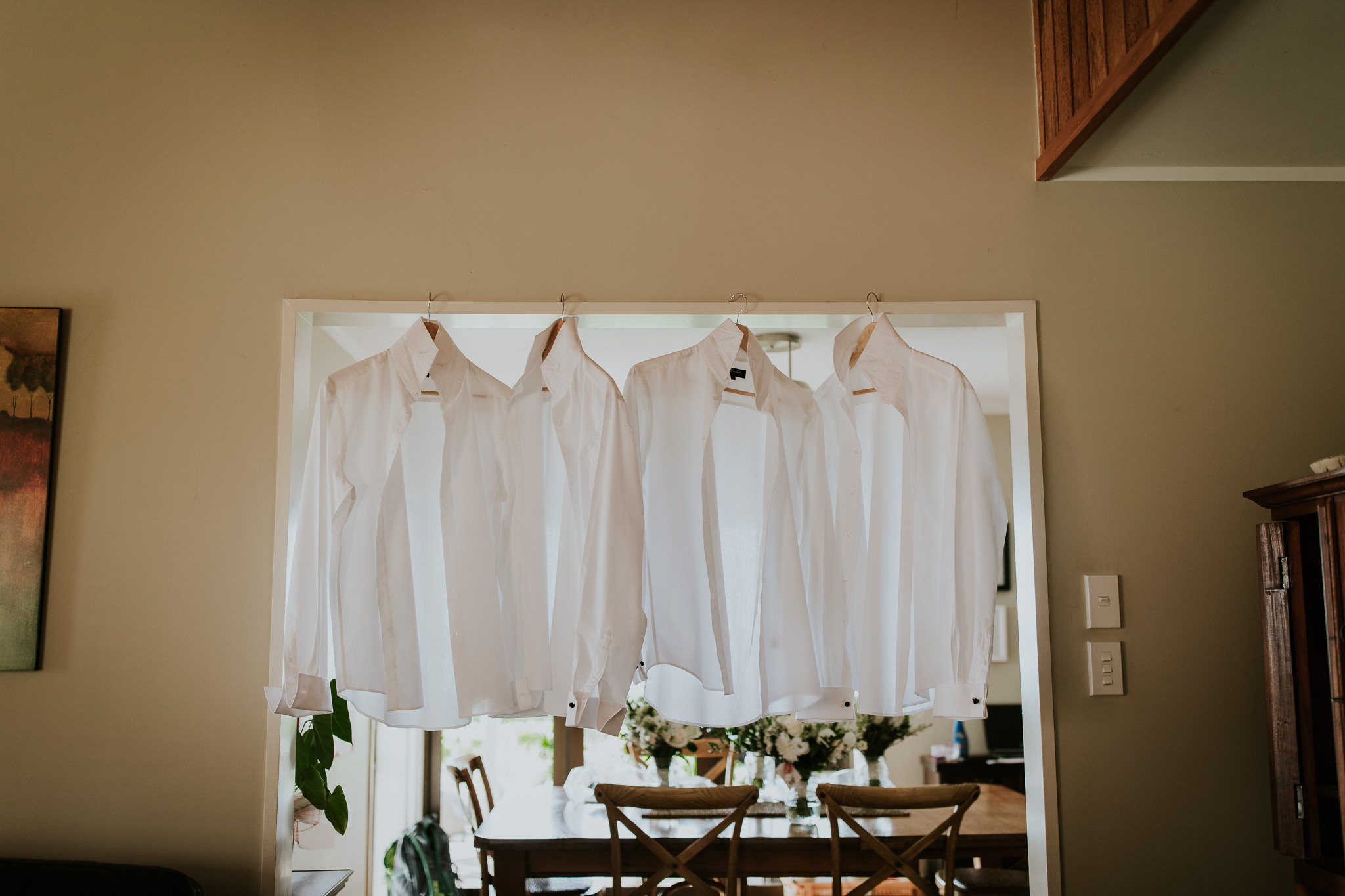 Groom and groomsmens shirts hanging in farm wedding getting ready spot.