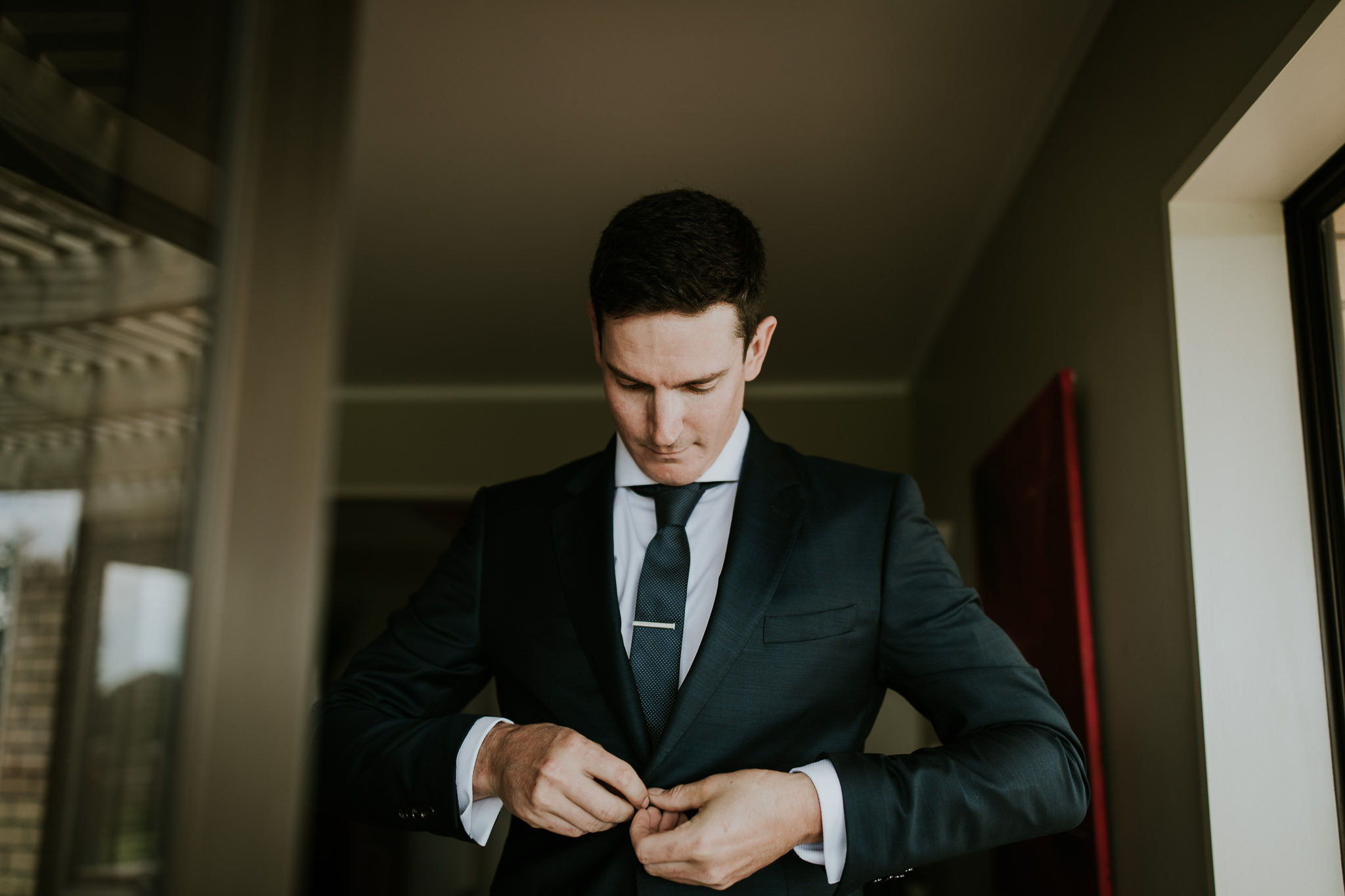 Groom doing up the last button on his suit before the wedding