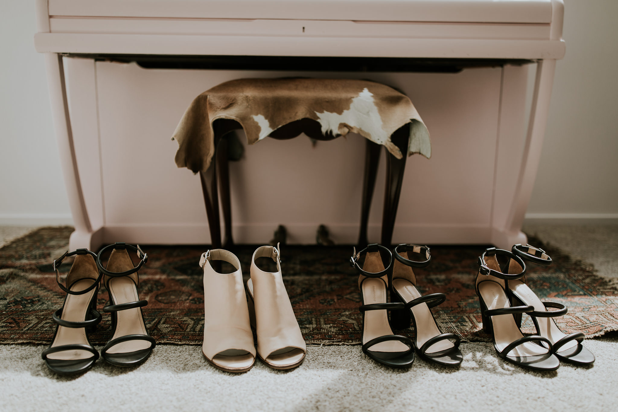Bride and bridesmaids shoes displayed on rug during getting ready on wedding day