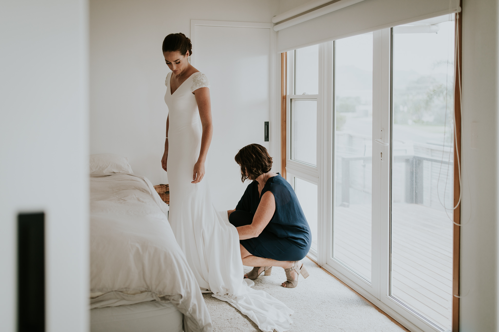 Mother of the bride helping bride get into elegant bridal gown on wedding day