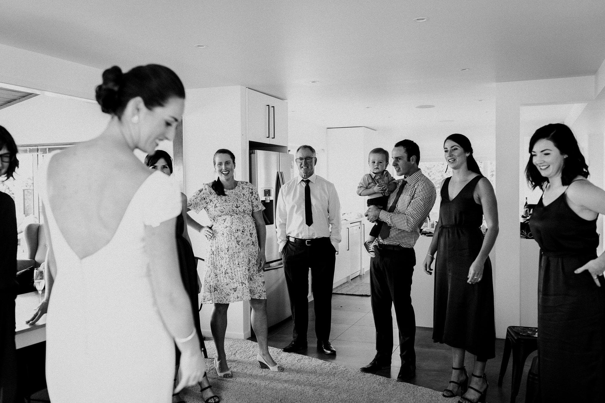 Bride showing family her dress with father of the groom smiling and laughing