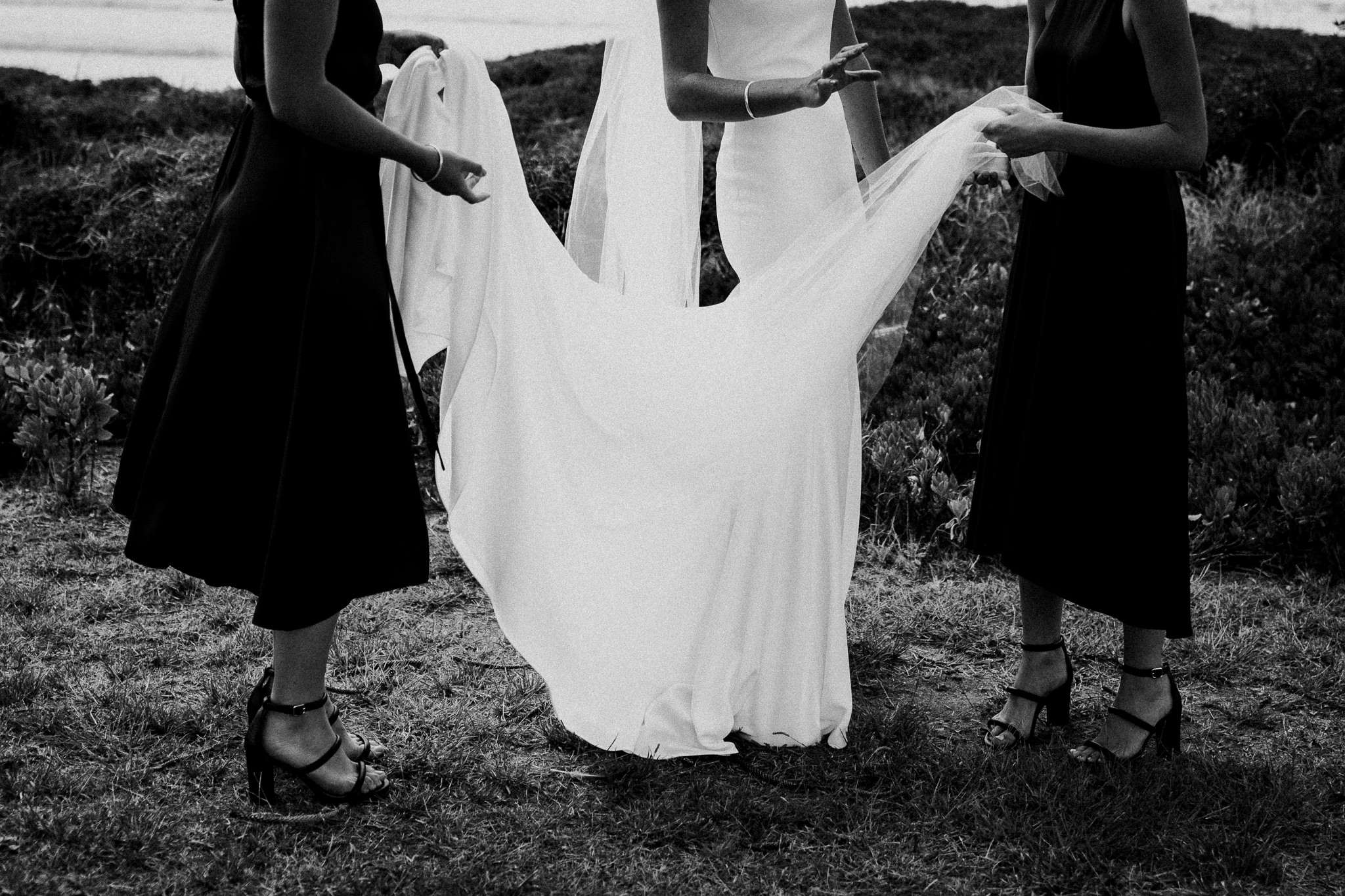 Bridesmaids straightening out bride's dress before wedding photos