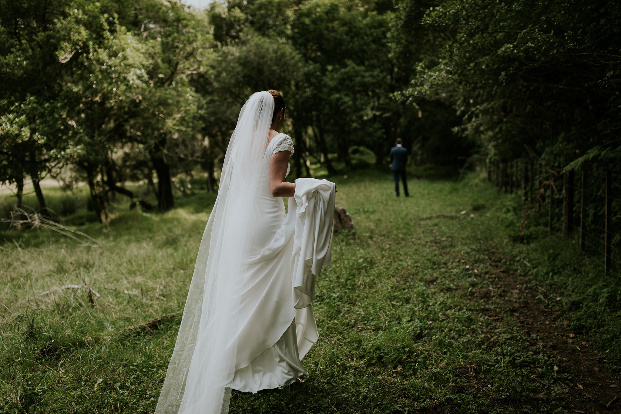 Kiwi bride walking towards groom carrying her wedding dress during first look at New Zealand farm