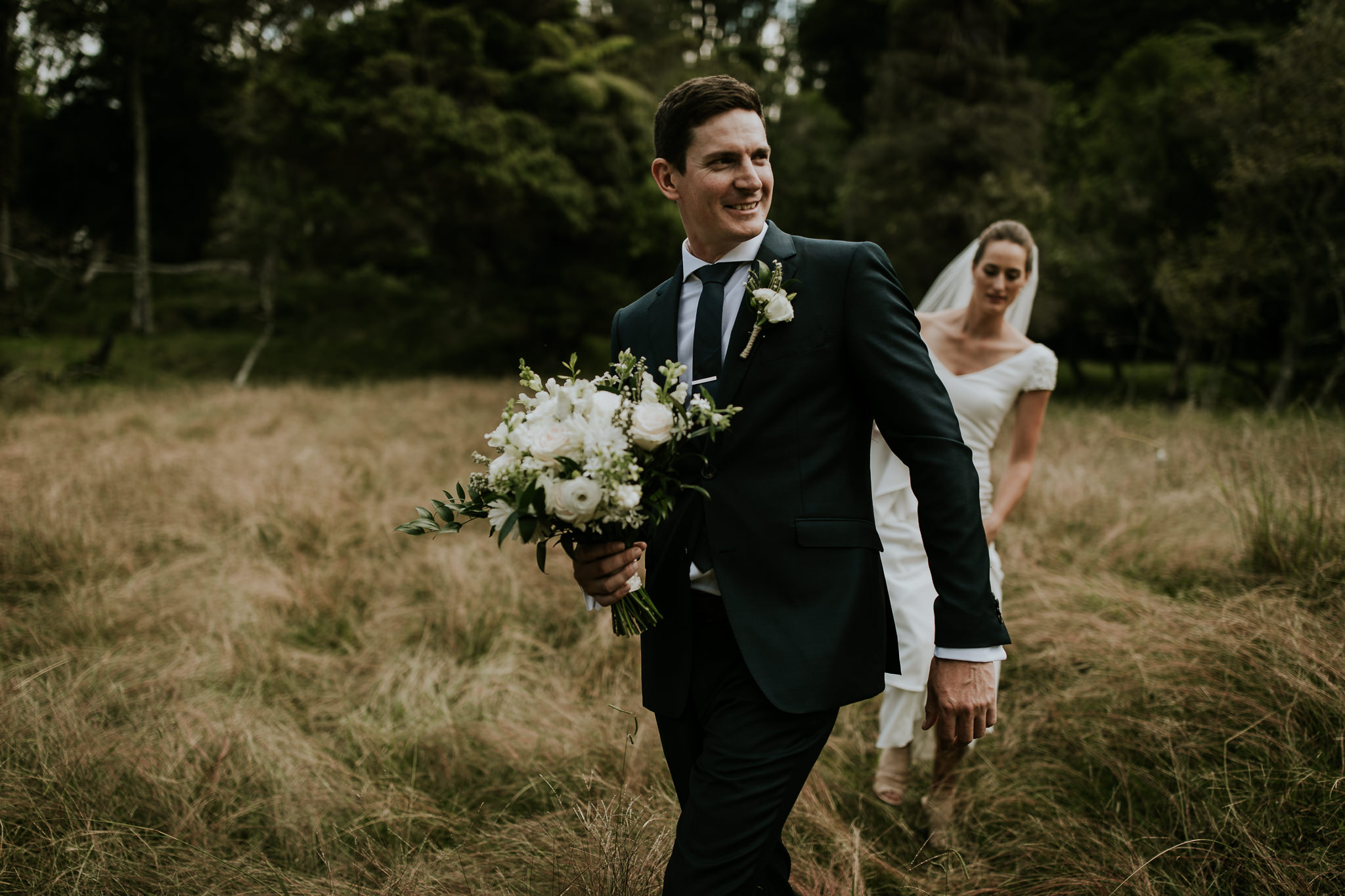 New Zealand groom holding bouquet and walking through field