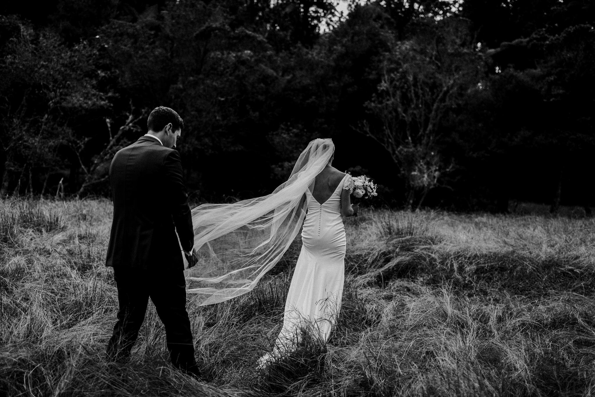 Black and white portrait of kiwi bride and groom walking through field for photos
