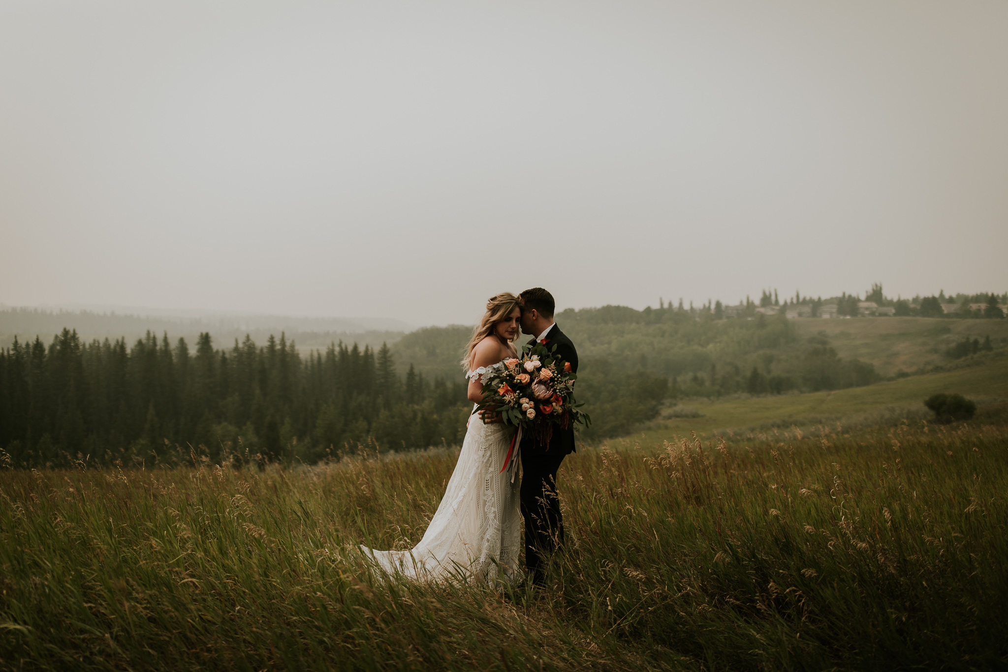 Romantic wedding photo of boho couple wearing Rue de Seine bridal gown and holding floral bouquet, embracing her husband in Fish Creek Park Calgary