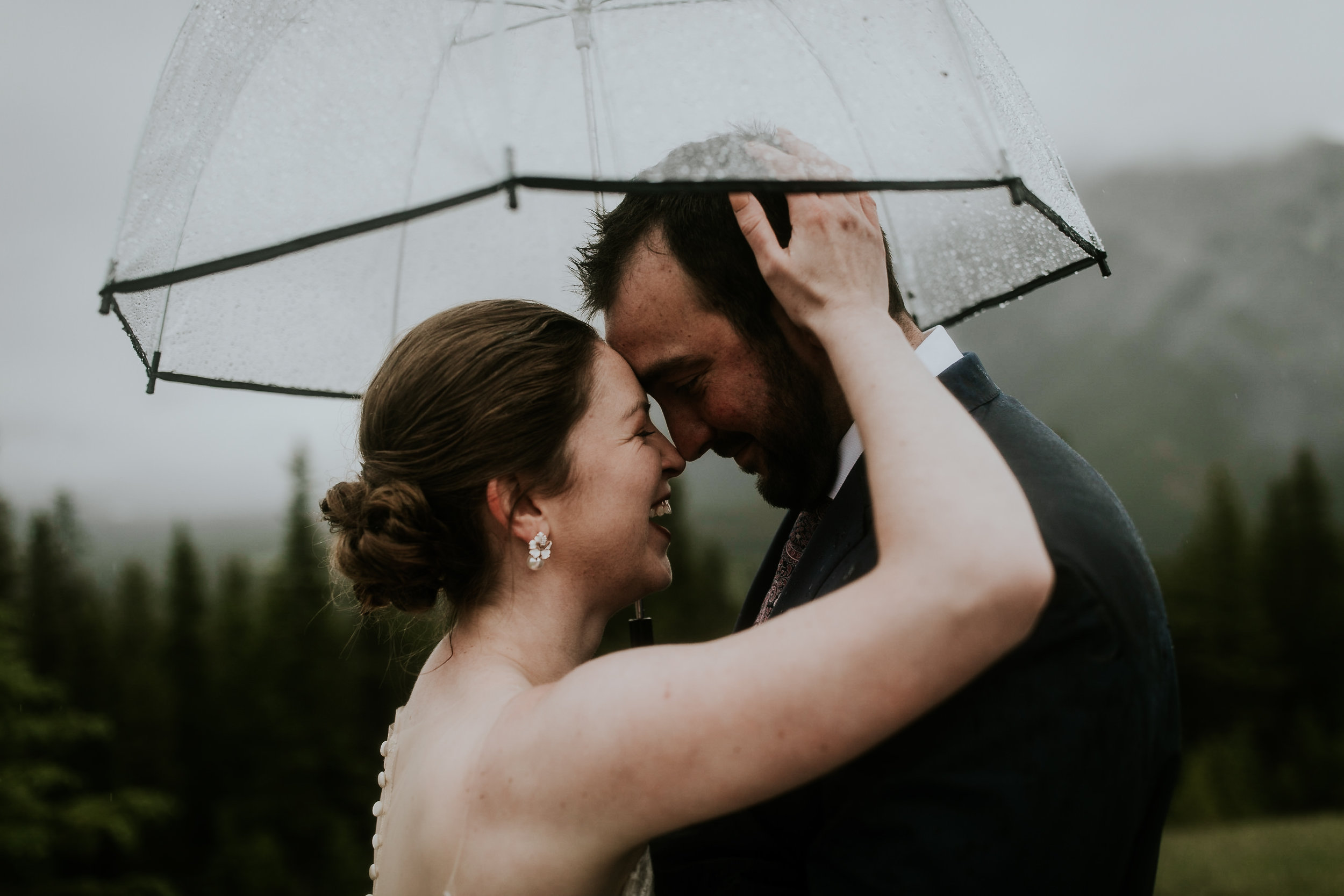 Newlywed couple embraces each other and smiling at each other underneath an umbrella during their rainy mountain wedding ceremony in Banff.