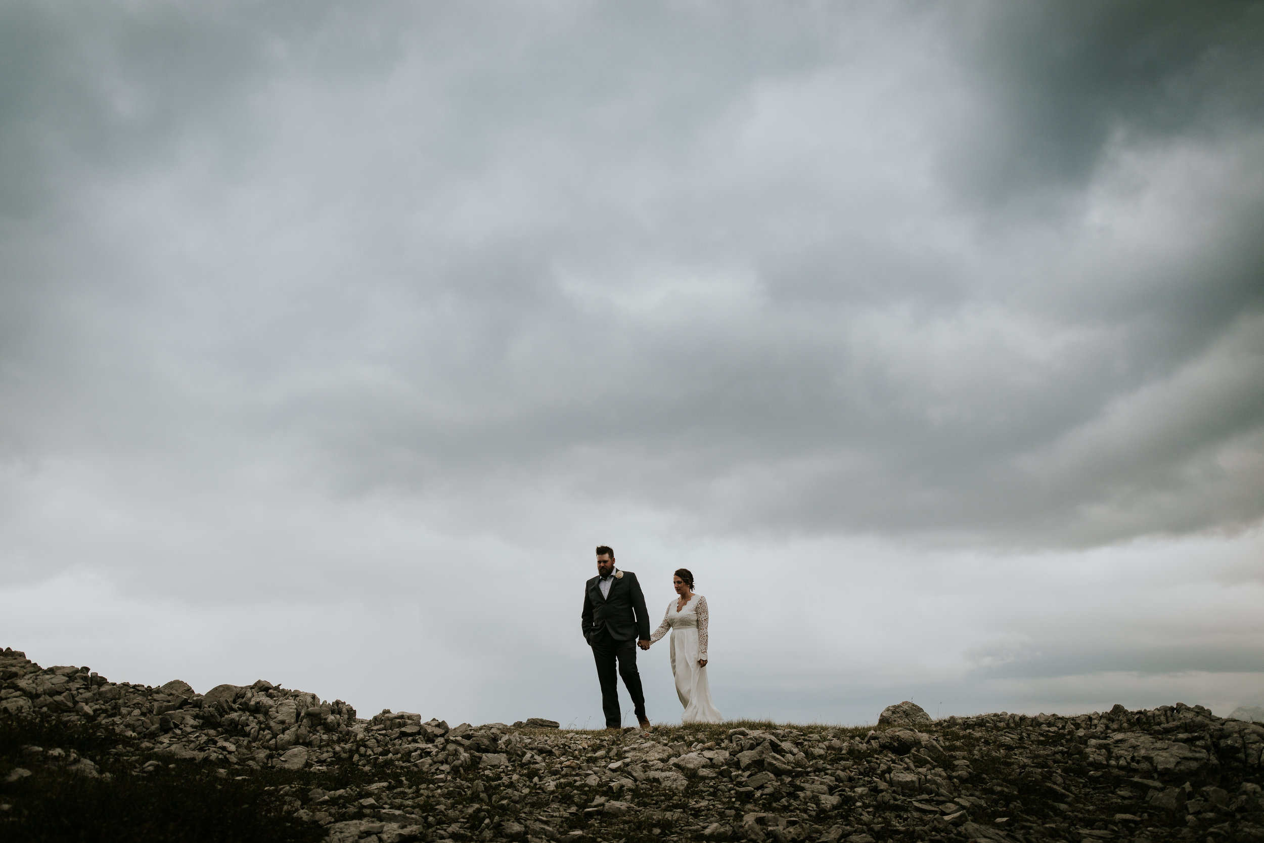 Epic helicopter elopement mountain shot with stormy sky in the background and husband and wife holding hands.