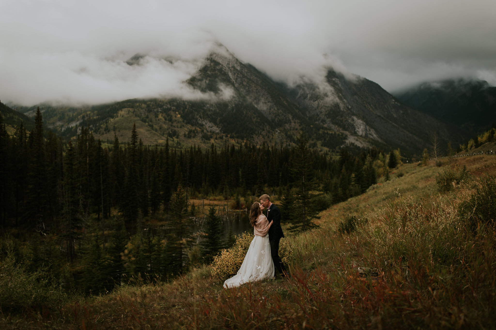 Boho bride and groom embracing on a mountainside during fall in Kananaskis Provincial Park with moody, cloud covered mountains in background.