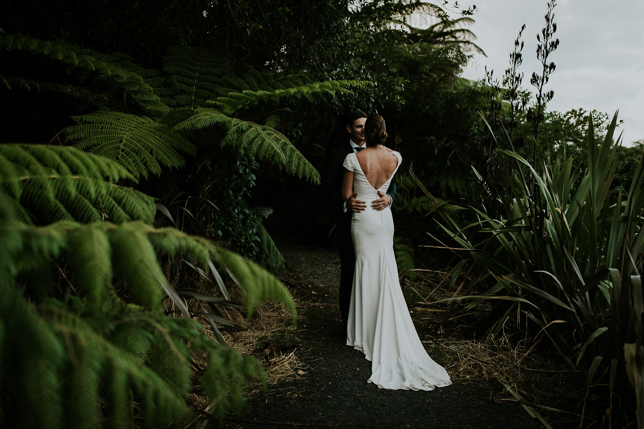 New Zealand destination elopement couple embracing among the ferns on KatiKati.