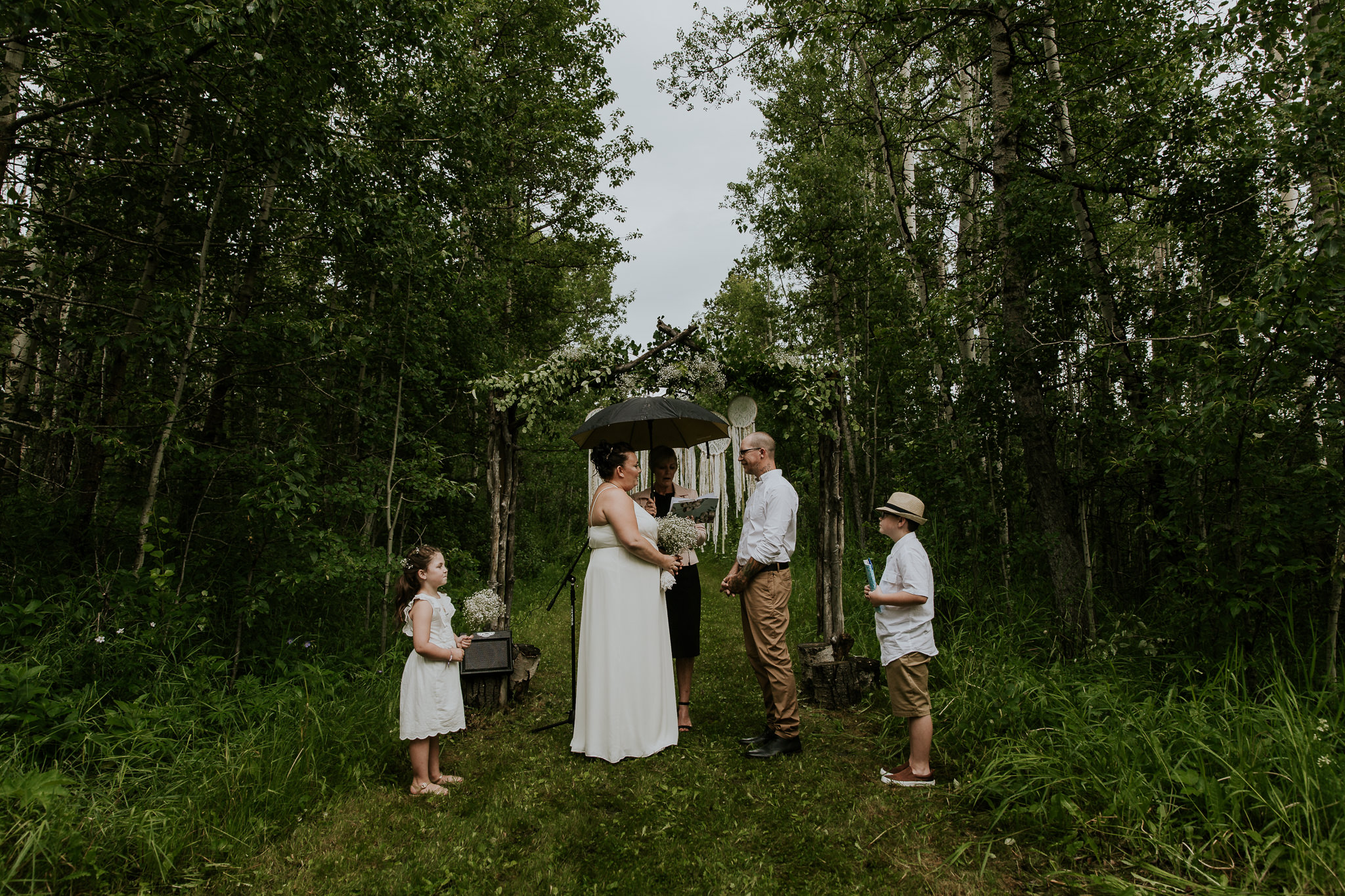 Intimate Bragg Creek backyard wedding ceremony with bride, groom and kids standing under DIY alter