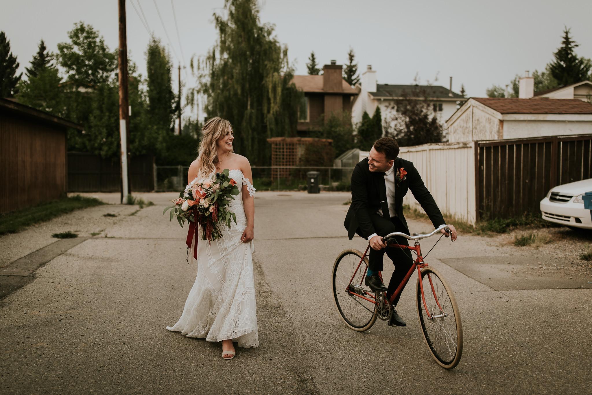 Boho bride walking down Calgary alleyway with groom riding bike beside her