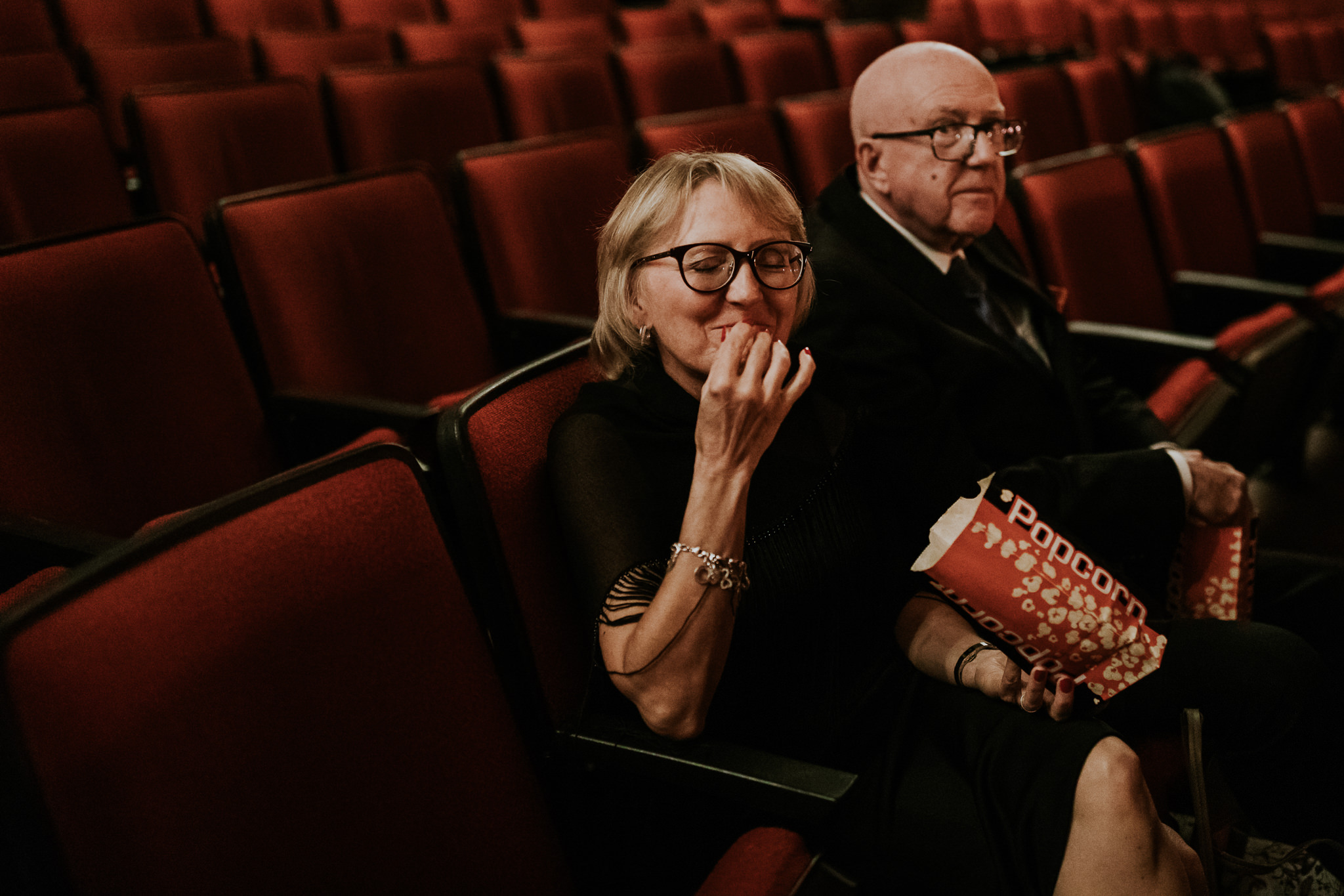 Mother of the bride eating popcorn at the Plaza wedding Calgary