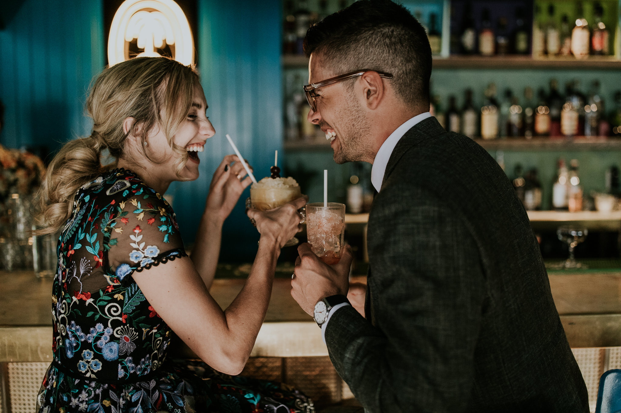Quirky bride and groom drinking tropical cocktails at Ricardo's Hideaway during wedding reception