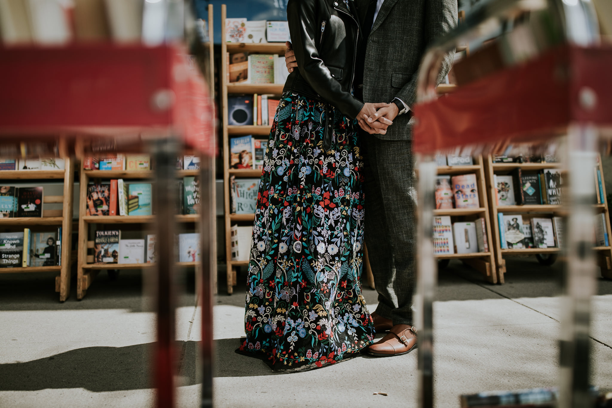 Bride and groom holding hands in urban wedding photos near bookstore downtown Calgary