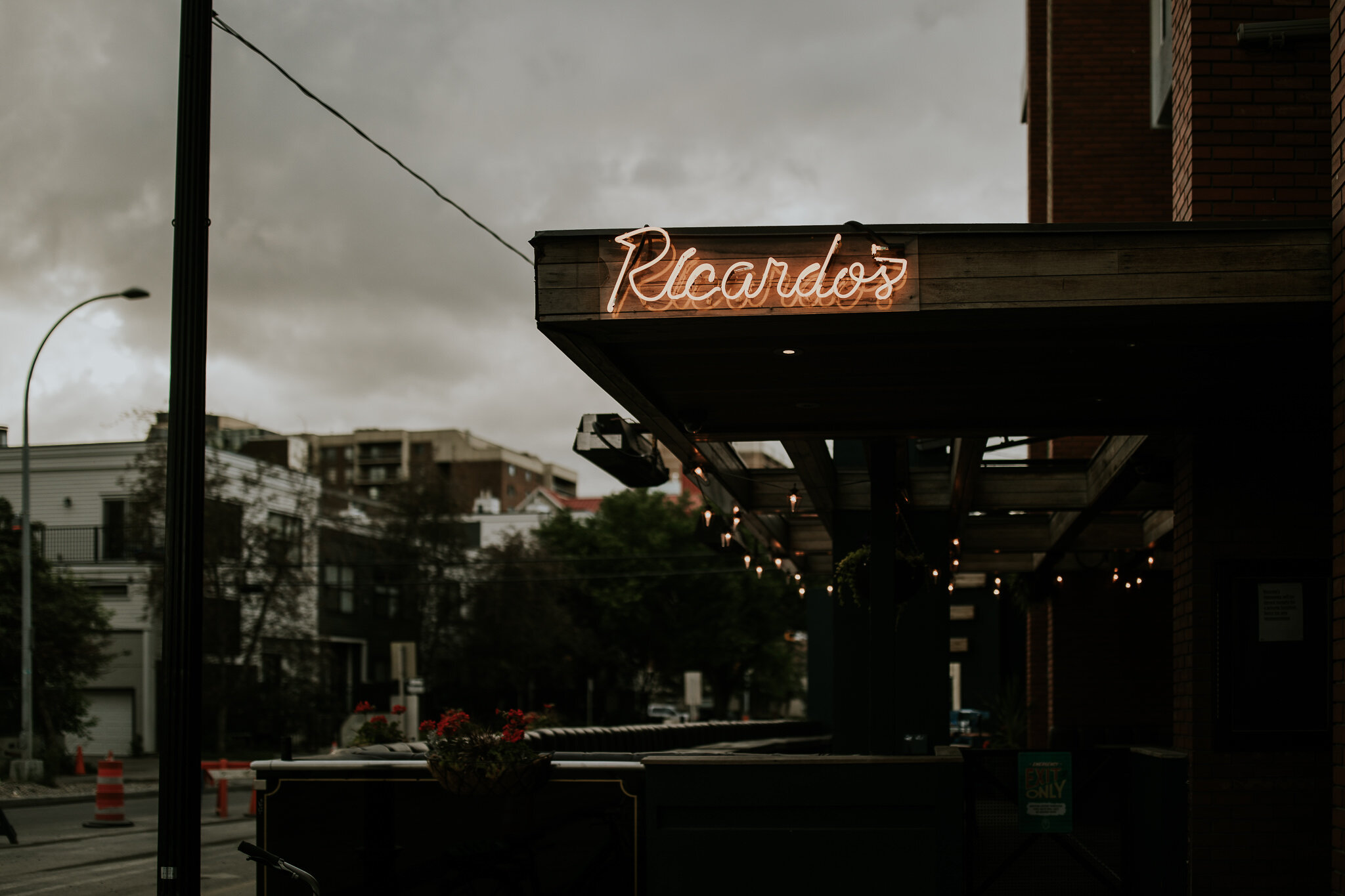 Ricardo's Hideaway sign lit up for intimate wedding reception while storm clouds roll in.