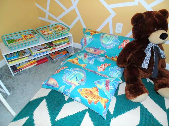 A custom floor pillow, made by Rylan's Nana, is perfectly cozy for curling up with books.