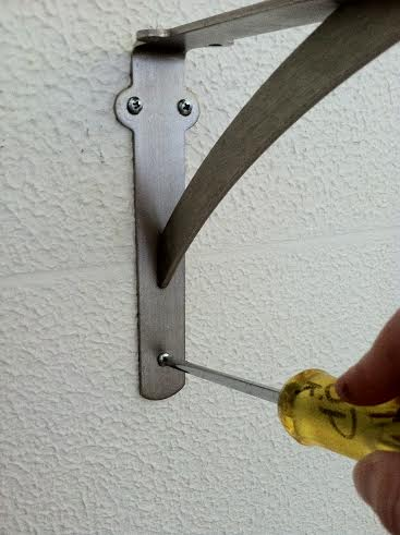 Once your toggle anchors are in, place the bracket over the anchors and screw the screws into the anchors.