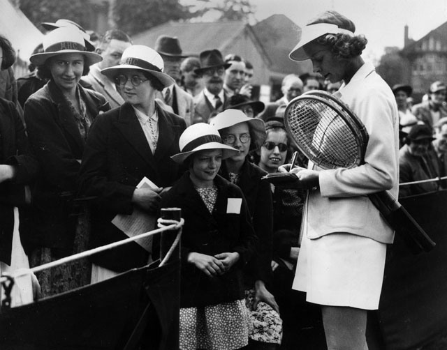 1937 American tennis player Alice Marble signs autographs for young fans