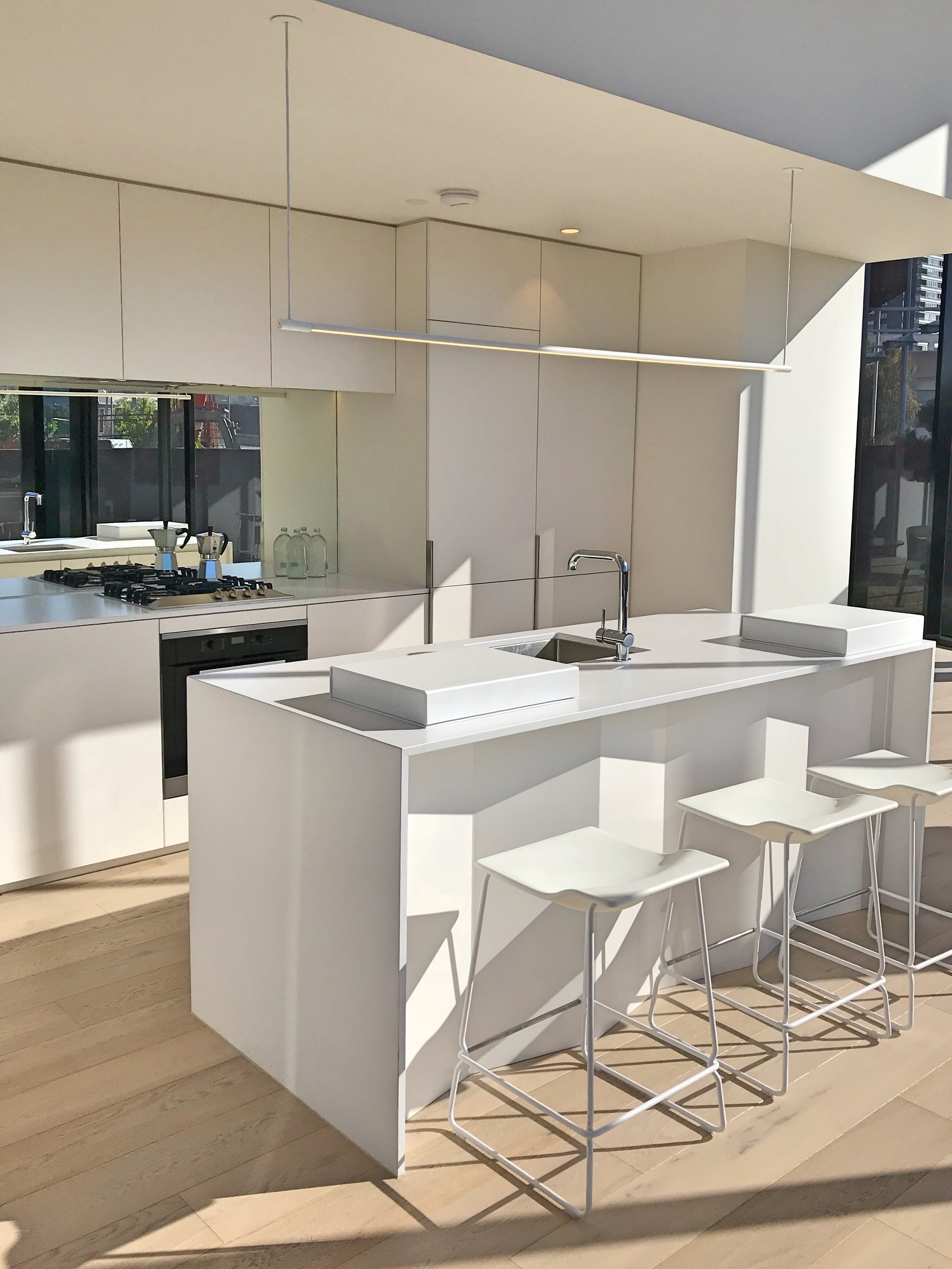 The beautiful all-white kitchen in the Melbourne Square display suite gleams in the morning sun.