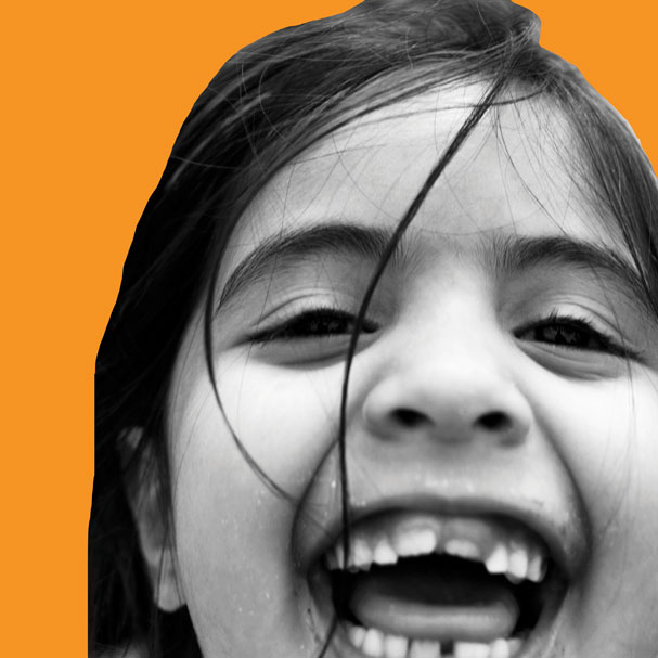 Girl-smiling-in-playground-square_orange-sm.jpg