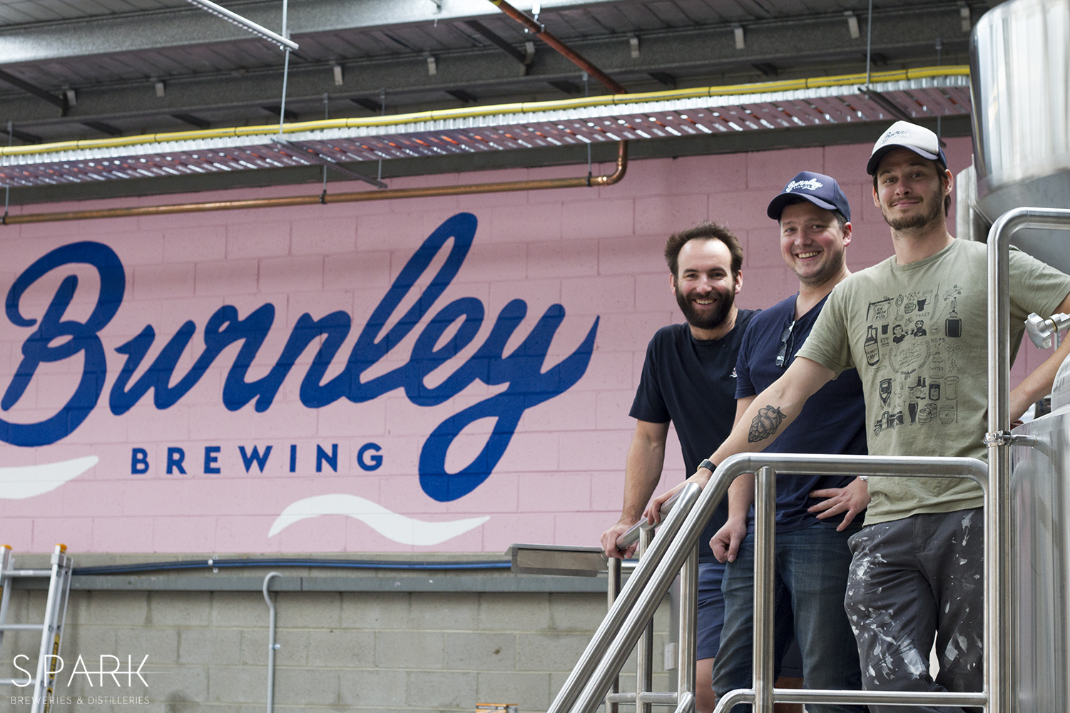 Phil, Neil and Michael from Burnley Brewing on the brewdeck of the 15hL system. Neil is wearing a matching Burnley cap