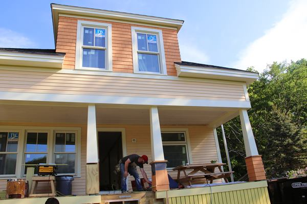 Another look at the front of the home. With upper level trim details complete, the crew is working on wrapping the front porch columns.