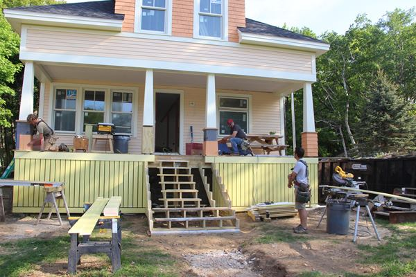 Mark Pollard, Shane Fenton, and Dale Cunningham work on porch stairs and columns in May.