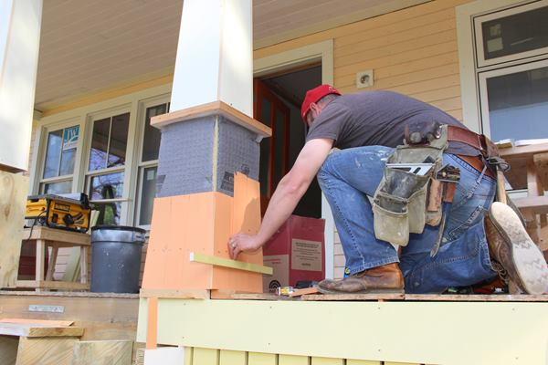 Fenton sets a cedar shingle in place on the post.