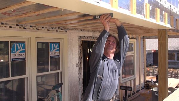Carpenter Dale Cunningham installs the front porch beam trim.