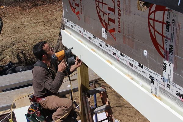 Pollard nails fascia to ¾-inch strapping applied over the foil-faced rigid insulation. Trim elements are spaced off the foil faced polyiso foam to facilitate the drainage of wind driven water and drying of the wood trim. The beam trim shown here is unusual, Pollard points out: it is the only trim or siding element on the building exterior where the space behind the trim has no air inlet at the bottom or exhaust at the top for air to flow freely. However, the air space behind the wood trim, combined with a coat of primer and first coat of paint, should still add to service life of the wood and the paint job.