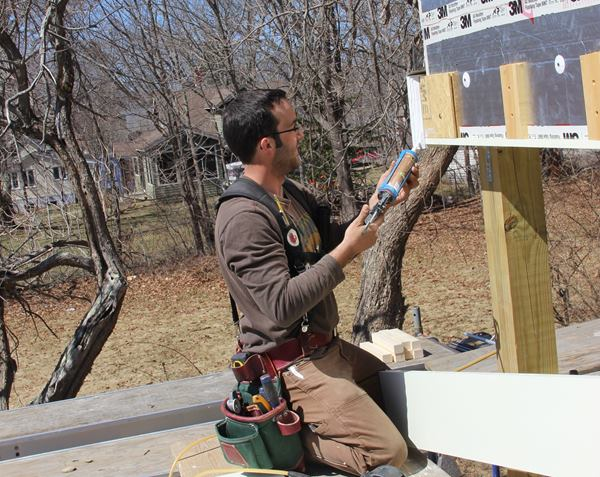 Project lead Mark Pollard applies a polyurethane sealant to the primed miter of the beam trim.