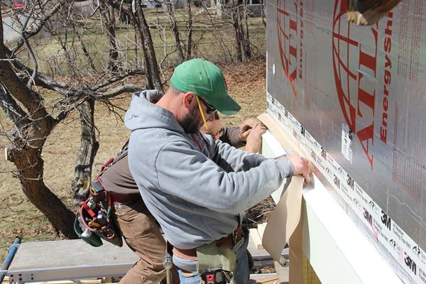 """Nailing the cap flashing to the wall sheathing through the 3"""" of continuous rigid foam is impractical; instead, Pollard and carpenter Shane Fenton seal the flashing to the face of the rigid insulation using 3M 8067 flashing tape."""