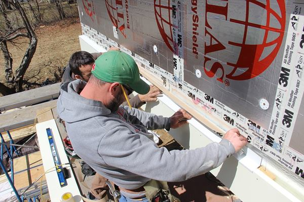 The acrylic adhesive tape is tenacious so care is taken to make sure the flashing is pitched for drainage before being pressed into place. The tape will be pressed into place with a hard rubber j-roller to further increase the bond of the adhesive.
