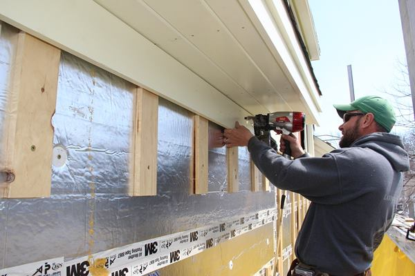 Fenton nails the frieze board over the plastic vent and 1x4 furring. The top edge of the clapboard siding will slide into the gap between the frieze and the 1x4's, leaving a 3/8-inch gap for the exhausting air.