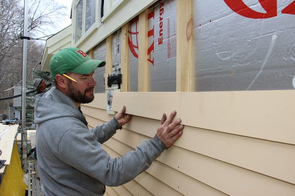 """Fenton """"dry fits"""" a clapboard. He will prime the end cut, then slip a square of asphalt paper behind the joint for secondary weather protection before pinning the end of the clapboard in place."""